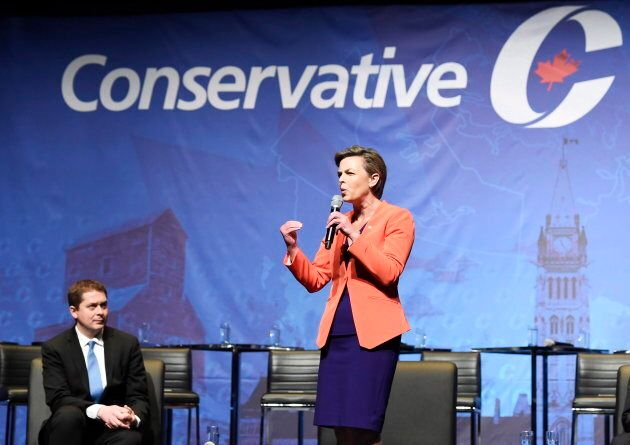 Kellie Leitch speaks as Andrew Scheer listens during the Conservative Party of Canada leadership debate in Toronto on April 26, 2017.