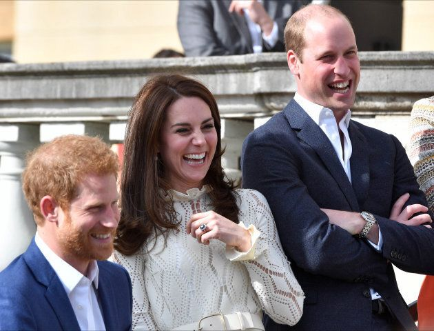 Prince Harry, Catherine, Duchess of Cambridge and Prince William, Duke of Cambridge laugh as they host a tea party in the grounds of Buckingham Palace.
