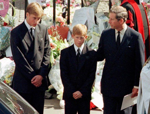 Prince Charles touches the shoulder of his son Harry as his other son Prince William watches the hearse bearing his mother Diana, Princess of Wales.