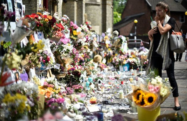A woman looks at flowers, tributes and messages left for the victims of the fire at the Grenfell apartment...