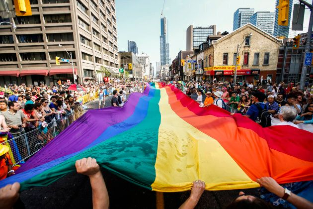 Revellers hold a giant pride flag during the