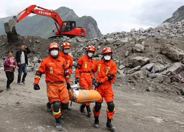 Rescue workers carry a victim at the site of a landslide that occurred in Xinmo Village, Mao County,...