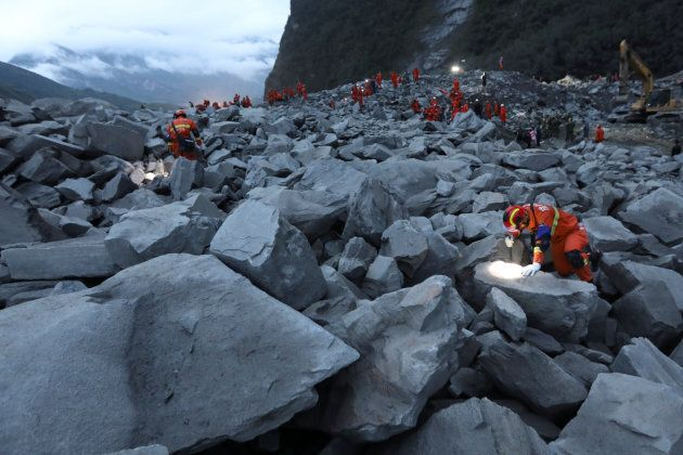 Rescue workers search for survivors at the site of a landslide that occurred in Xinmo Village, Mao County,...