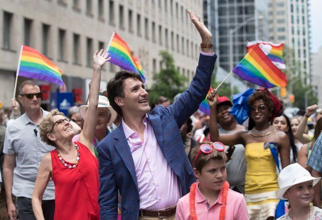 Prime Minister Justin Trudeau and Ontario Premier Kathleen Wynne wave to the crowd at the Pride parade...