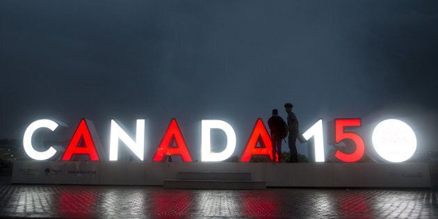 Tourists stand near an illuminated 'Canada 150' sign in Niagara Falls, Ontario, Canada, on Wednesday,...