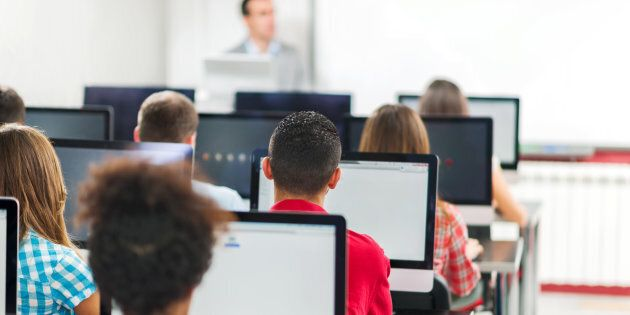 Rear view of lager group of people at a computer class. Teacher is teaching in the