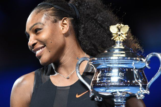 Serena Williams of the US holds up the trophy following her victory over Venus Williams of the US in...