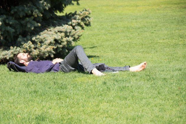 A man sneaks a nap under the spring sun in Toronto's Queen's