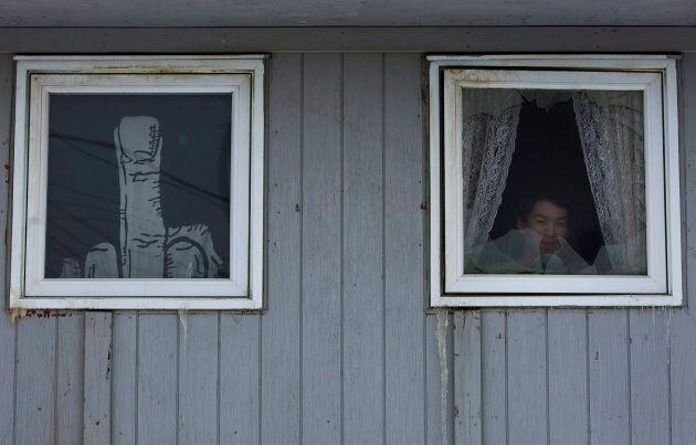 A Inuit person looks outside his window in Iqaluit in the Nunavut Territory of Canada on Wednesday, April...