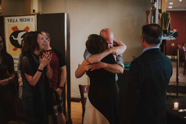 Eric, the father of the bride, sharing a hug with Jackie, the mother of the groom, as Karen, the stepmother of the bride, and Troy, the father of the groom, watch on.