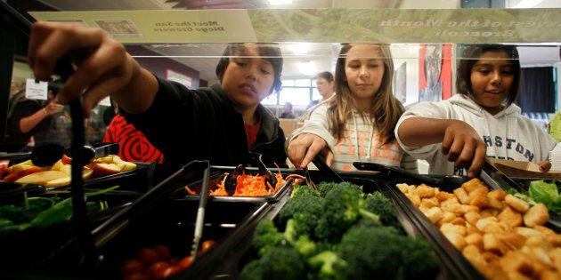 Students get their lunch from a salad bar at the school cafeteria in San Diego,