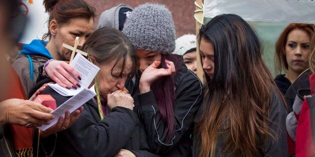 Family members embrace one another as protesters rally outside Edmonton's City Hall on Thursday, April...