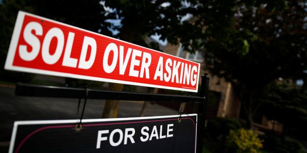 A real estate sign stands in front of housing in Vaughan, a suburb in Toronto on May 24,