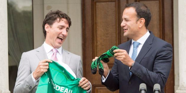 Prime Minister Justin Trudeau reacts as he is presented with a jersey and socks by Irish Taoiseach Leo...