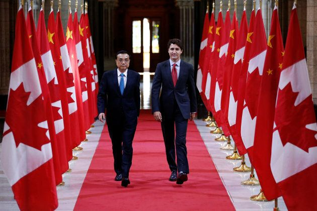 Prime Minister Justin Trudeau and Chinese Premier Li Keqiang walk in the Hall of Honour on Parliament...