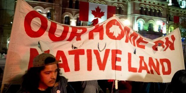 People hold up a sign during a demonstration on Parliament Hill, as a crowd gathered to erect a teepee...