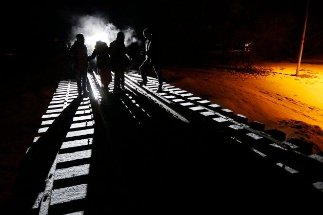 Migrants cross into Canada from the United States by walking down a train track early Sunday, Feb. 26,...