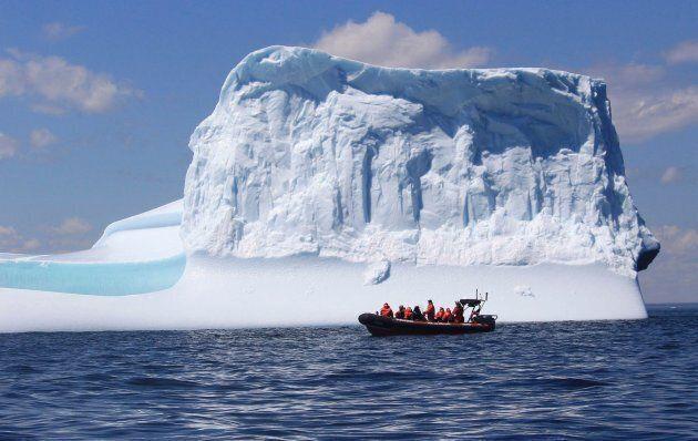 A tour boat cruises pass an iceberg off the coast of Bonavista,