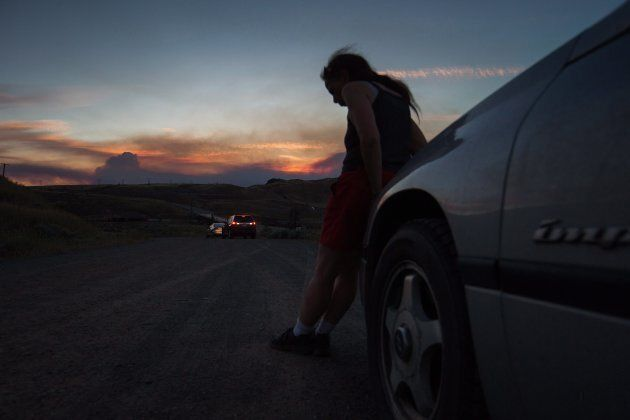 A woman who was evacuated from Cache Creek rests on the front of her car along the Trans-Canada Highway...