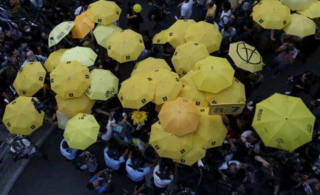 Pro-democracy protesters carrying yellow umbrellas, a symbol of the Occupy Central civil disobedience movement, are stopped by the police as they try to break the cordon line outside government headquarters in Hong Kong, China Sept. 28, 2015.