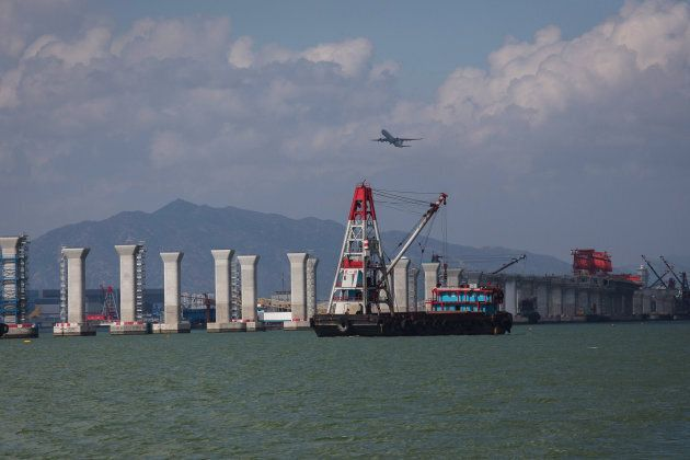 A transport barge travels past the Hong Kong-Zhuhai-Macau Bridge (HZMB) as it stands under construction in Hong Kong, China, on June 28, 2015.