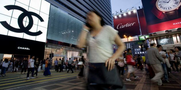 Pedestrians walk past a Chanel outlet in Hong Kong,