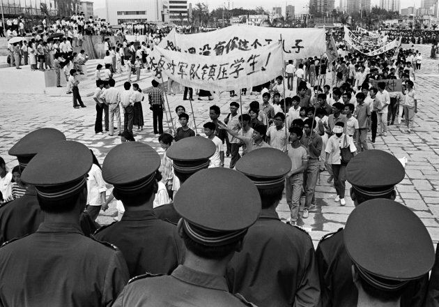 Chinese police monitor a march by tens of thousands of pro-democracy protesters in the special economic zone of Shenzhen in southern China on May 22, 1989. Hundreds of people were killed in Beijing on June 4, 1989 when Chinese troops crushed month-long pro-democracy demonstrations which attacked government corruption.
