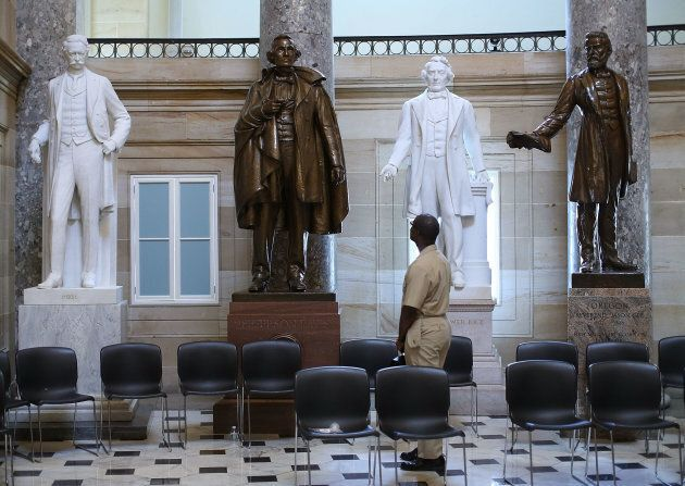 U.S. Navy Lt. William Edmund Newsome looks at a bronze statue of Confederate president Jefferson Davis (2ndL) that stands inside of Statuary Hall at the US Capitol June 24, 2015 in Washington, D.C. Some members of Congress are calling for the removal of the statue of the Confederate president from inside of the Capitol.