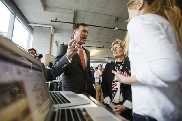 Bill Morneau, Canada's finance minister, centre left, speaks as Kathleen Wynne, premier of Ontario, center right, looks on during a demonstration at the MaRS Discovery District in Toronto, Ont. on March 30, 2017. A new institute for artificial intelligence research opened with funding from the federal and Ontario governments as well as the private sector.