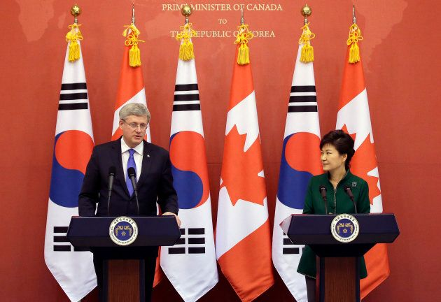 Canadian Prime Minister Stephen Harper (L) answers questions from reporters as South Korean President...