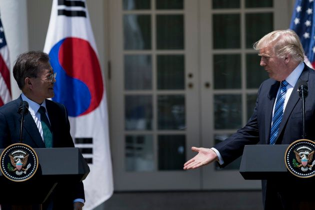 U.S. President Donald Trump reaches to shake the hand of South Korea's President Moon Jae-in after making...