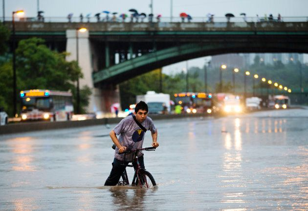 A man rides his bicycle during a flood on the Don Valley Parkway, a major highway, during a heavy rainstorm in Toronto, July 8, 2013.