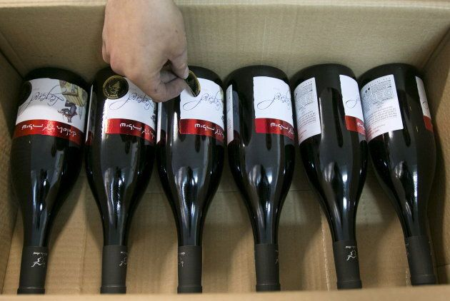 A worker places stickers on wine bottles while packaging them for export at Shiloh Wineries, north of...