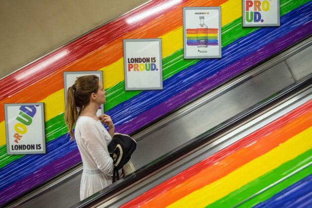 A woman rides a tube escalator decorated with the Pride flag colours on July 5, 2017 in London, England....