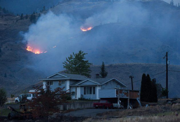 A wildfire burns on a mountain in the distance behind a house that remains standing on the Ashcroft First...