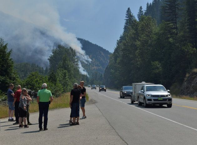 Tourists from Denmark stop to photograph one of several wildfires burning near Little Fort, B.C. on July...