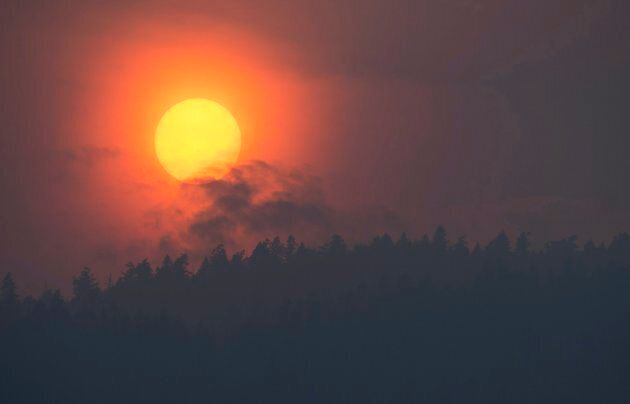 Smoke is seen rising in front of the sun as a wildfire burns near Little Fort, B.C. on July 11,