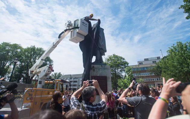 A Halifax City staff member covers the Edward Cornwallis statue with a black tarp as activists protest in Cornwallis Park in Halifax on Saturday, July 15, 2017.