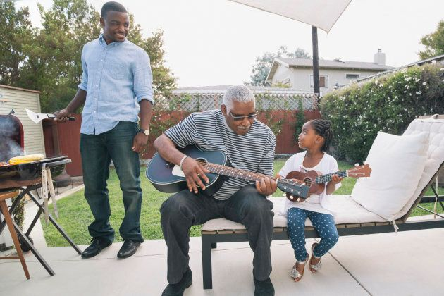African American grandfather teaching granddaughter to play