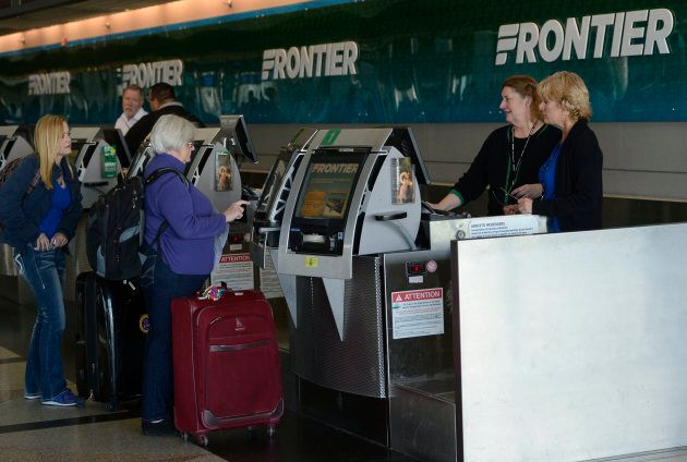 Frontier Airlines customer service agents help customers at the ticket counter at Denver International...