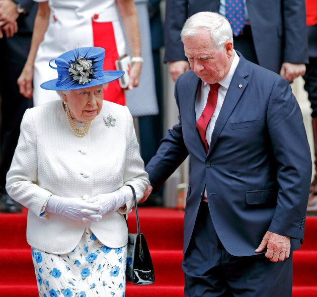 Gov. Gen. David Johnston holds Queen Elizabeth II's arm as she departs Canada House after attending a...