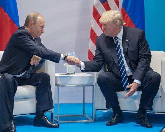 Russian President Vladimir Putin and President Donald Trump shake hands during a meeting at G20 Summit...