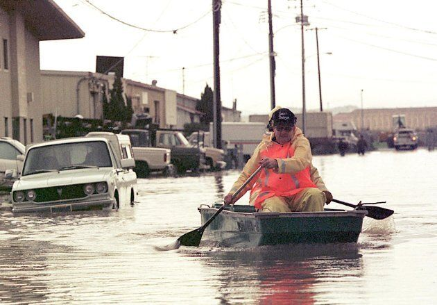 Firefighters paddle through a flooded street in Marin County, California. The county is experiencing...