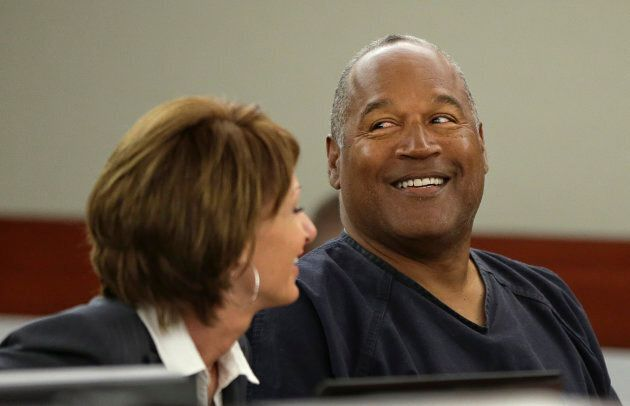 O.J. Simpson smiles as he sits with his attorney, Patricia Palm in Clark County District Court during...