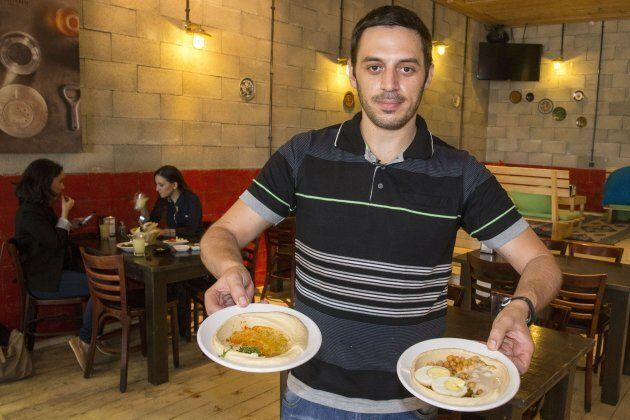Kobi Tzafrir, the owner of Hummus Bar in the central Israeli town of Kfar Vitkin, displays plates of...