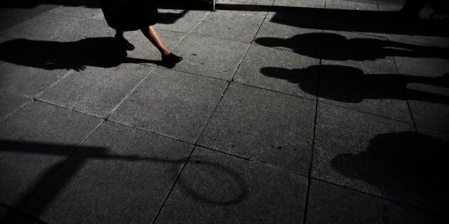 Shadows are seen as a woman walks down Bay Street in the financial district in Toronto, March 11,