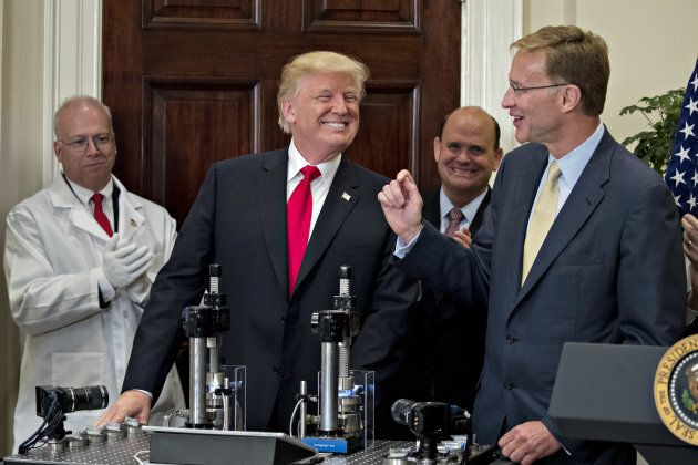 U.S. President Donald Trump smiles after participating in a glass strength test of a Corning Valor vial...