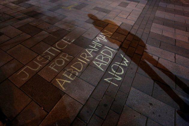 A man casts a shadow near a message written in chalk during a vigil for Abdirahman Abdi in Ottawa, July...