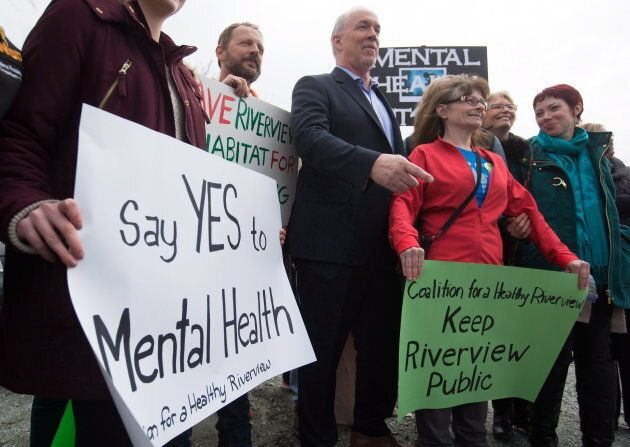NDP Leader John Horgan stands with mental-health advocates after an election campaign announcement about...