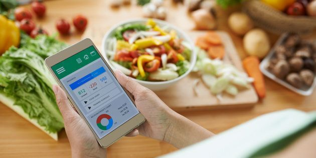 Woman using calorie counter application on her smartphone.